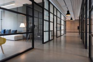 A photo of an office hallway with glass walls.